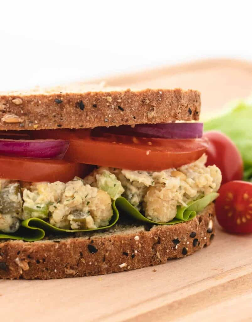 chickpea salad sandwich with sliced tomatoes and red onions
