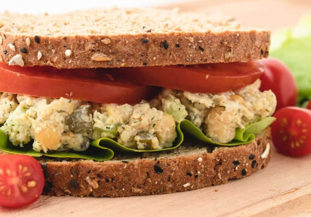 chickpea salad sandwich with sliced tomatoes and lettuce