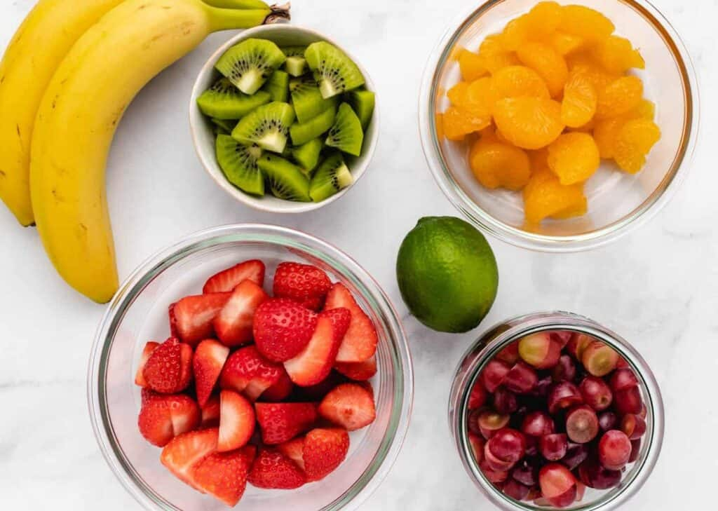 ingredients for a fruit salad, banana, kiwi, mandarin oranges, strawberries, grapes, and lime
