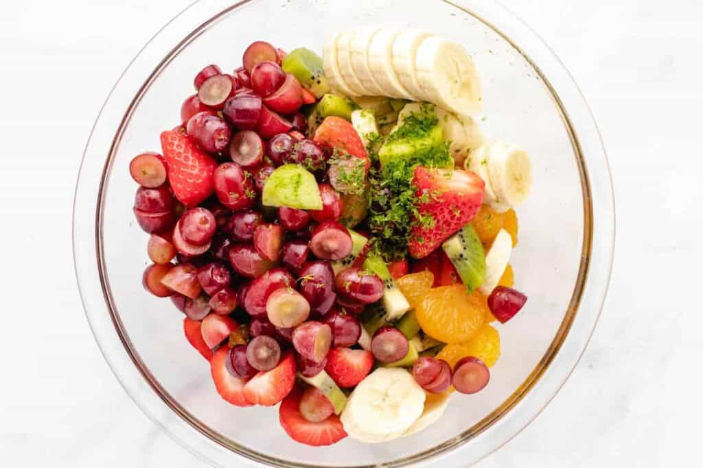 ingredients for a fruit salad in a glass bowl