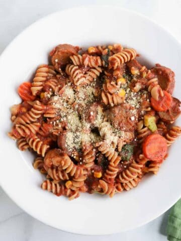 whole wheat pasta dish with red sauce, vegan sausages and vegetables