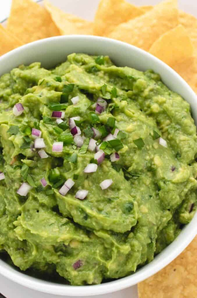 vegan guacamole in a bowl with tortilla chips