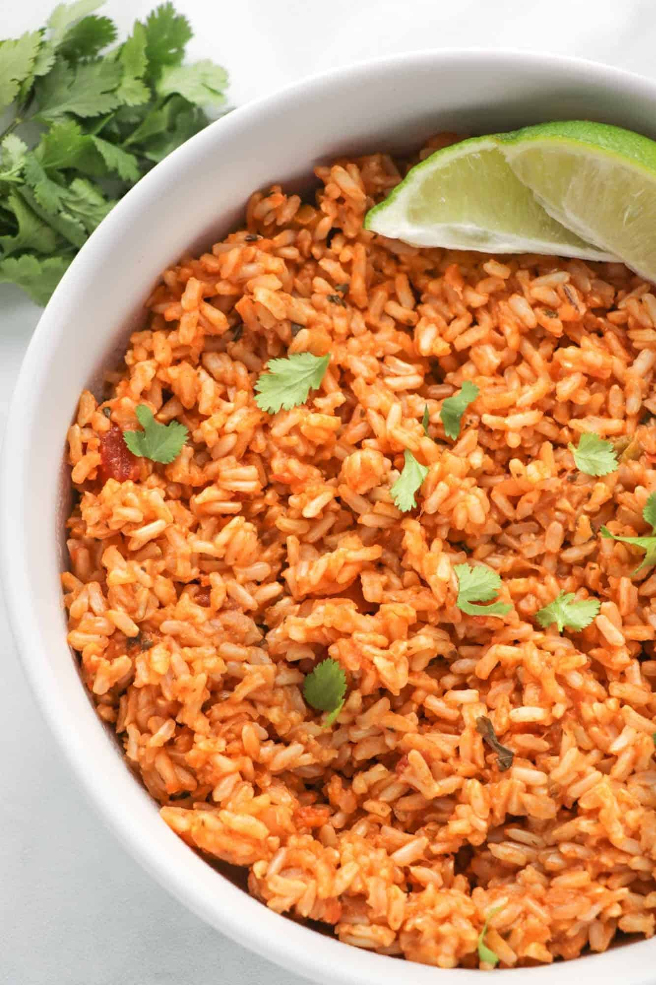 mexican inspired brown rice in a bowl with cilantro and a lime