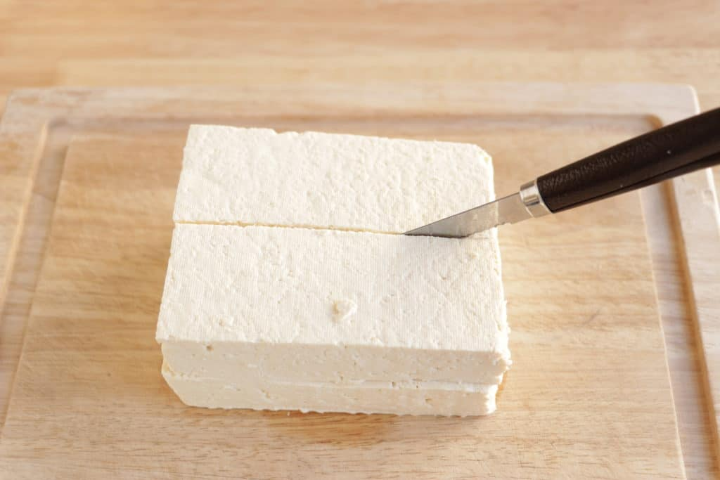tofu on a cuttin board being sliced in half
