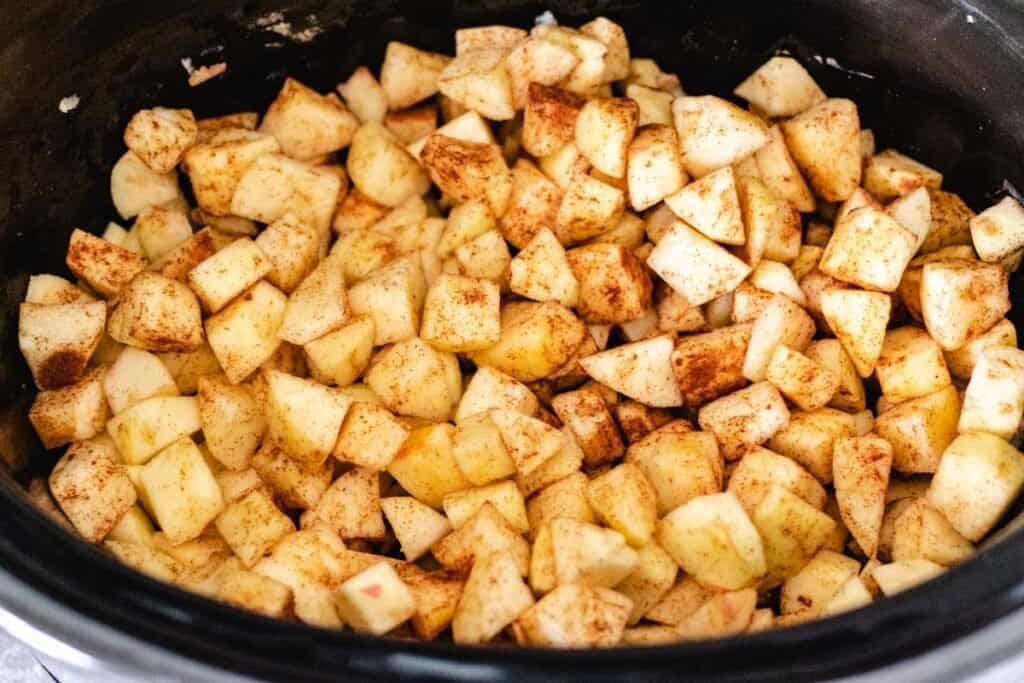 uncooked dice apples with cinnamon in slow cooker