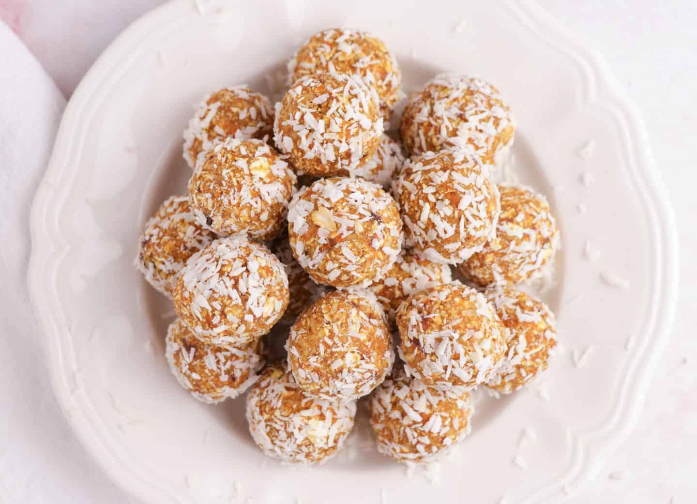 carrot cake energy balls coated in shredded coconut on a white plate.