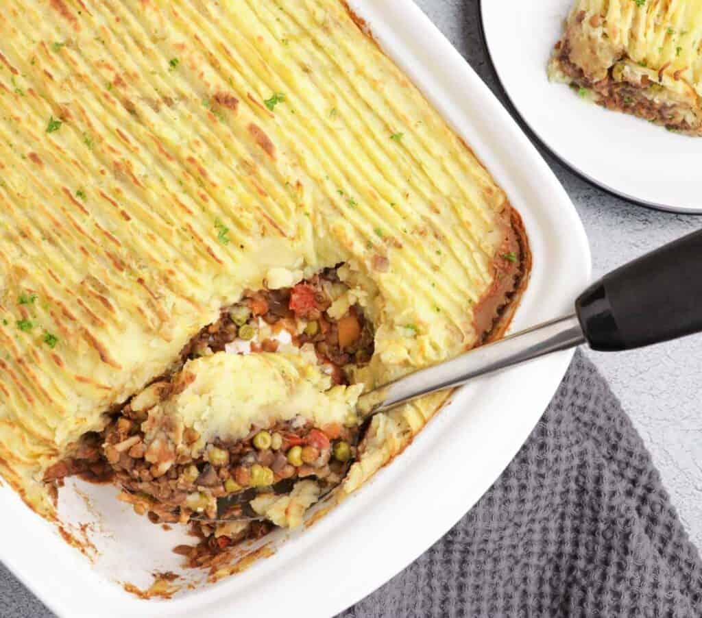 vegan shepherd's pie in a casserole dish with a serving spoon