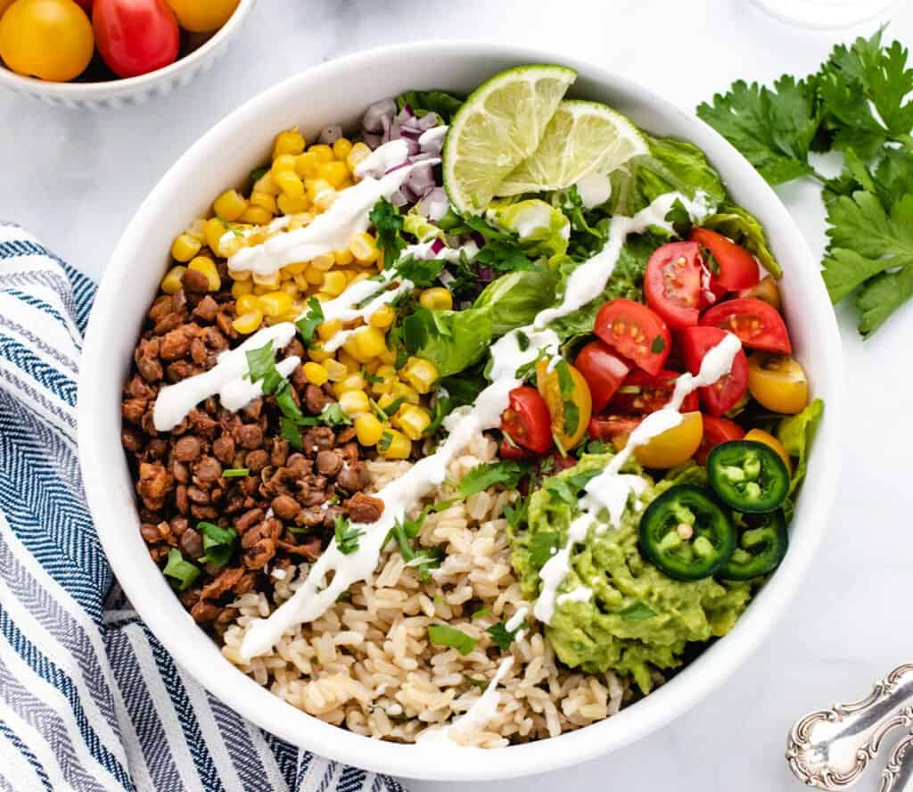 vegan taco bowl with lentil taco meat, brown rice, limes, corn, tomatoes in a bowl
