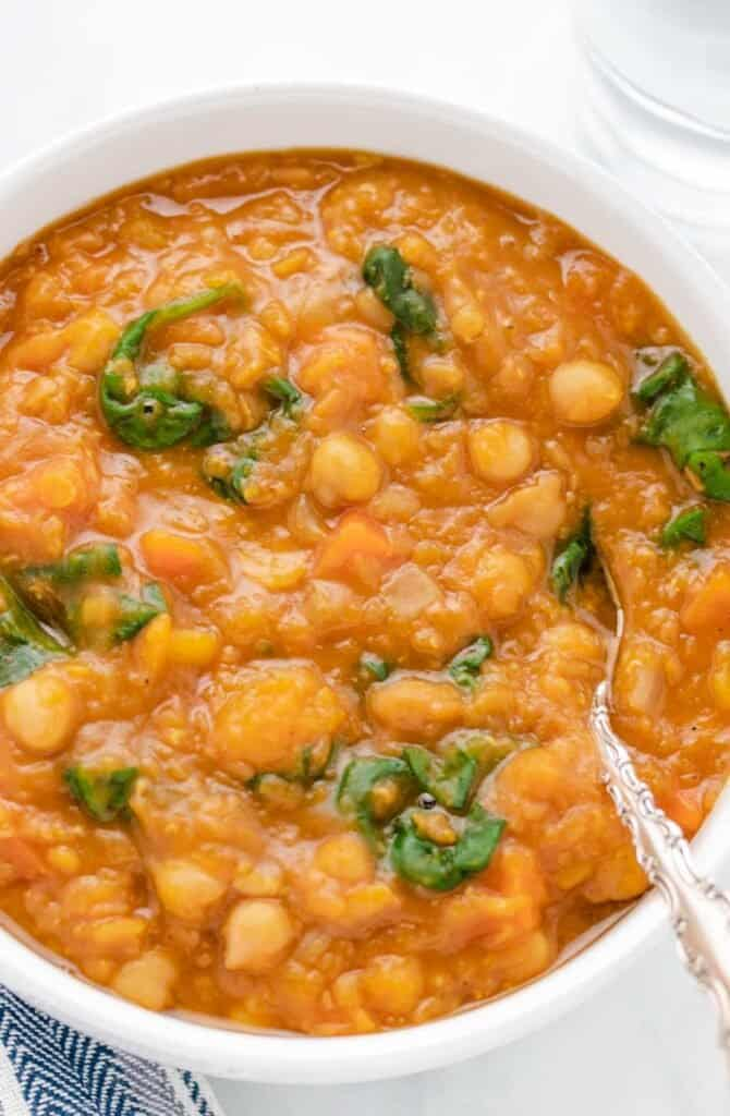 butternut squash and chickpea soup in a white bowl with a spoon