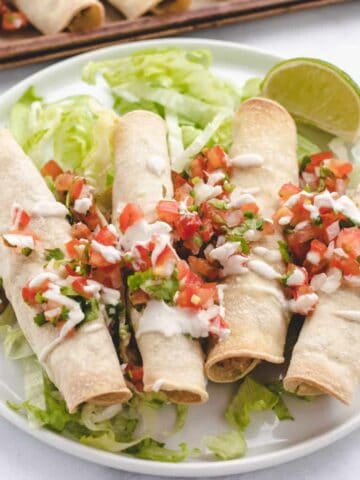 refried bean taquitos on a plate with lettuce and Pico de Gallo