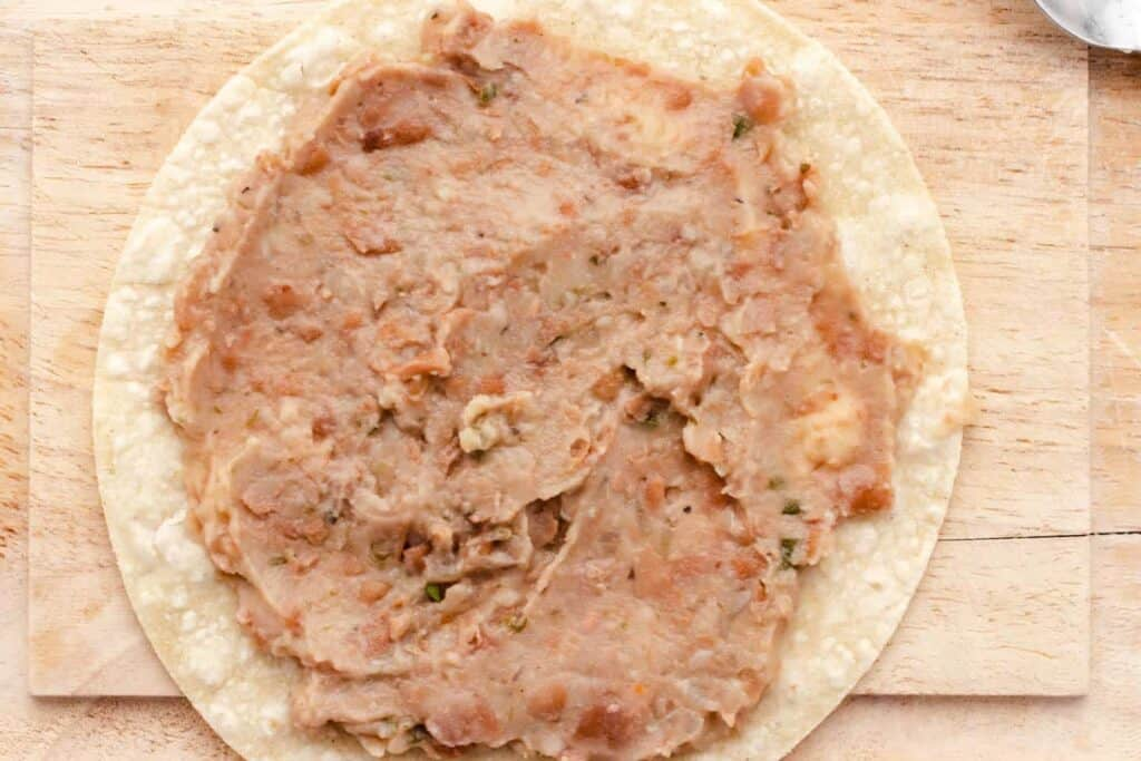 refried beans spread out on a tortilla