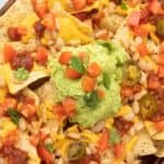 vegan nachos with cheese, diced tomatoes, pickled jalapeños, salsa, and avocado