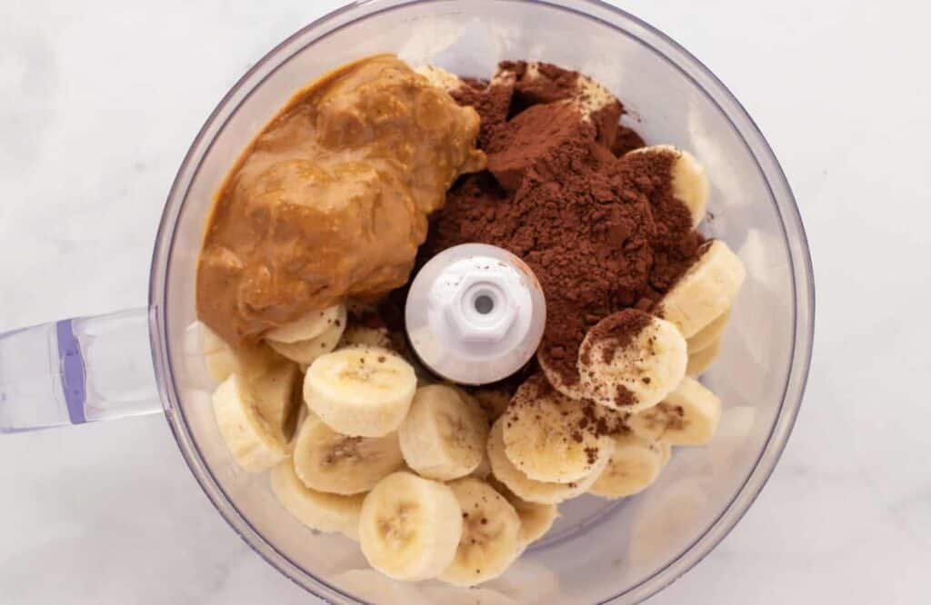 ingredients in a food processor for chocolate peanut butter nice cream