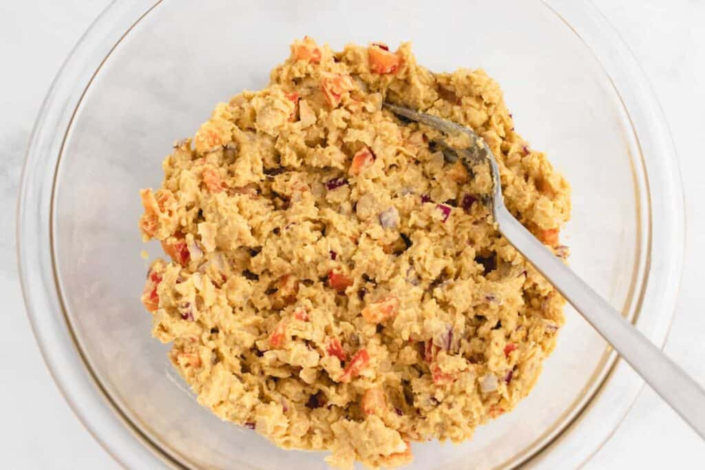 mashed chickpeas in a bowl with curry powder, red bell peppers, and red onion