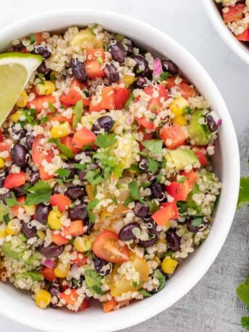 quinoa salad with black beans and a lime wedge in a white bowl