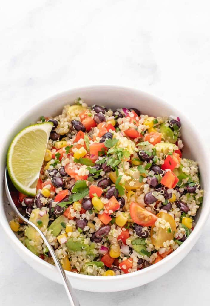 quinoa salad with black beans and lime wedges in a bow