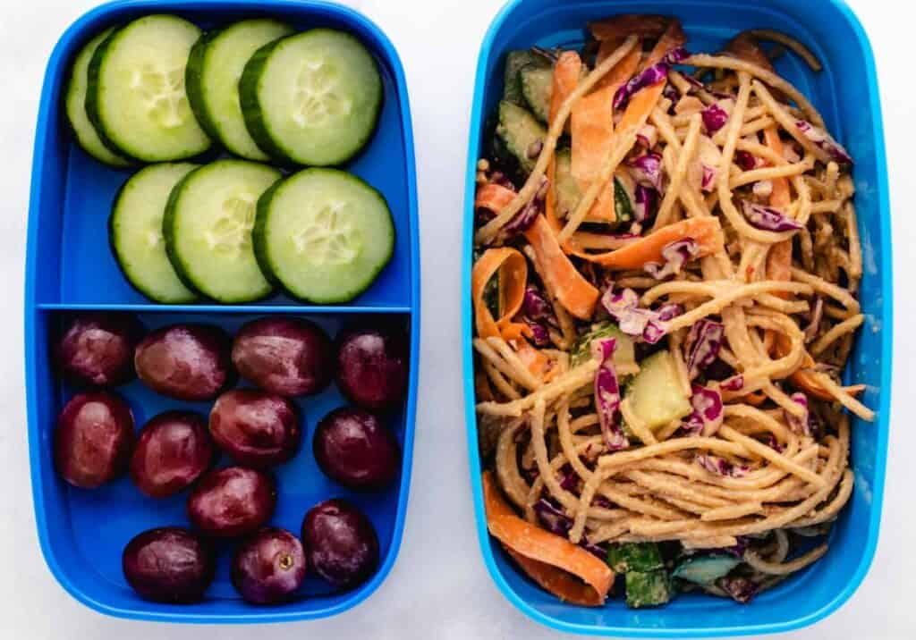 Peanut pasta with cucumber, carrots, and red cabbage in a bento box
