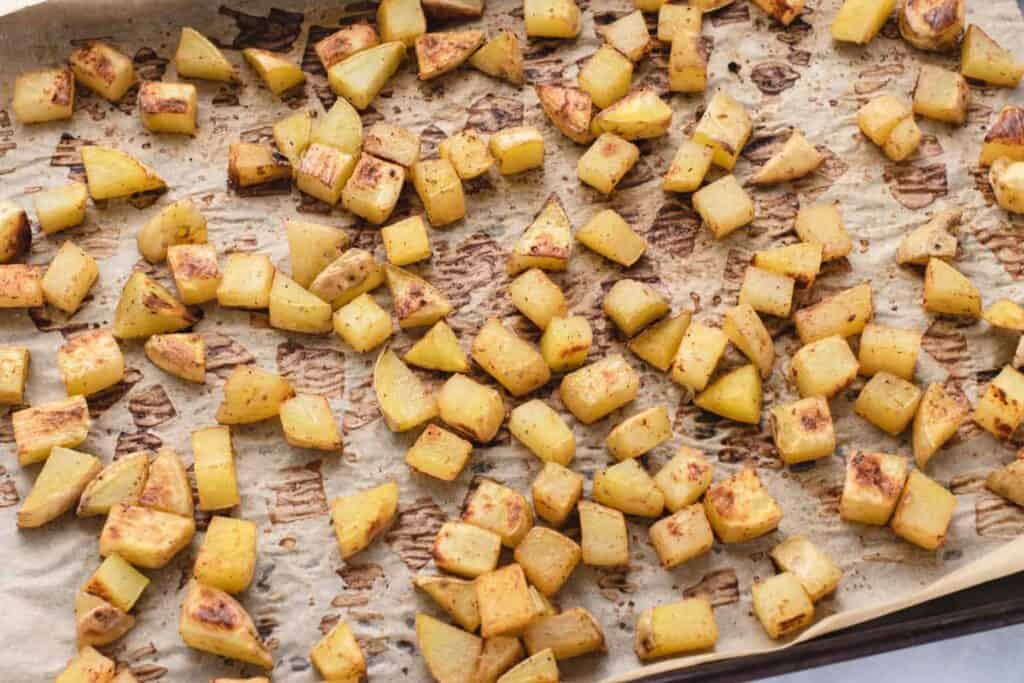 oil free roasted diced potatoes on parchment paper