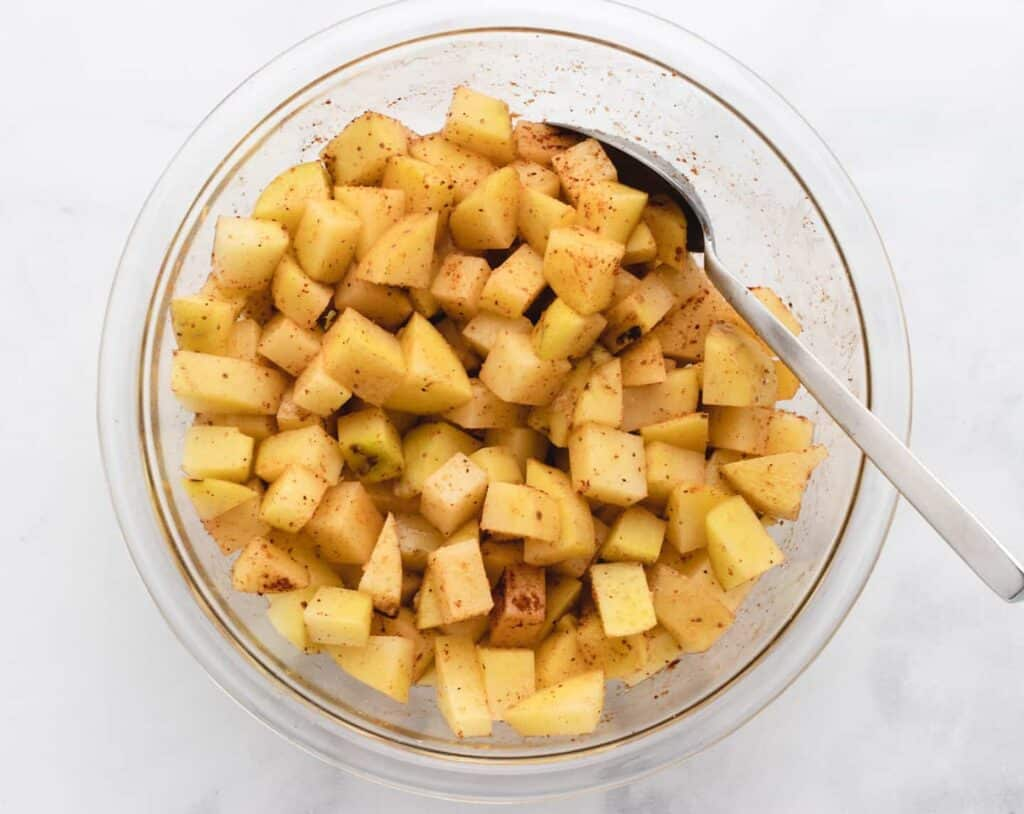 diced uncooked potatoes in a bowl with seasonings
