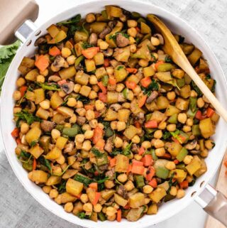 Vegan potato hash with peppers, mushrooms and chickpeas in a skillet