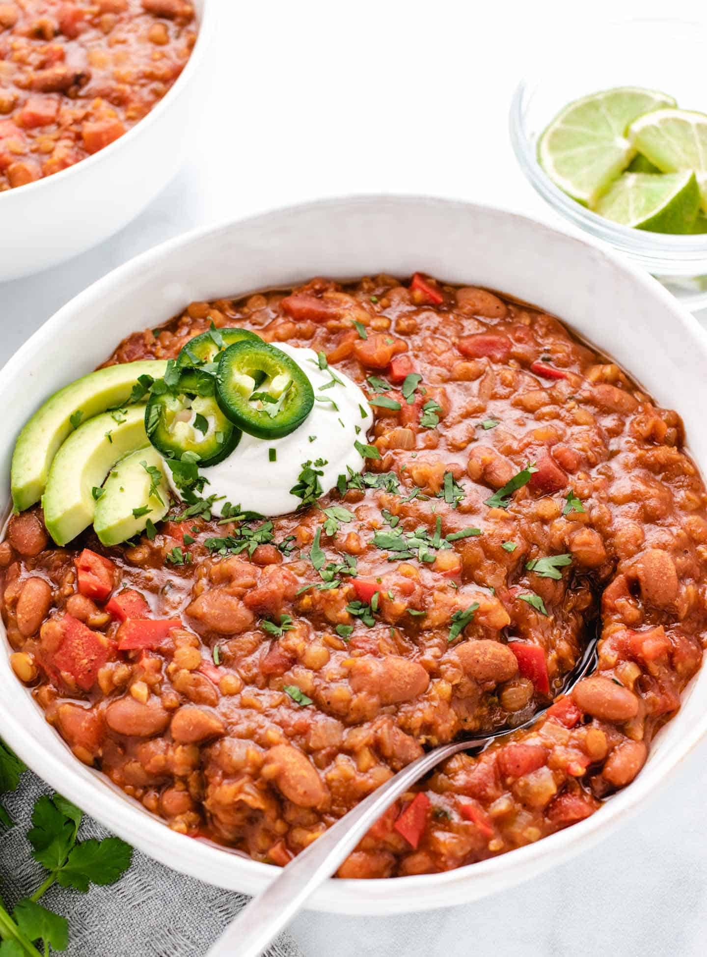red lentil chili with a spoon with avocado and jalapeños