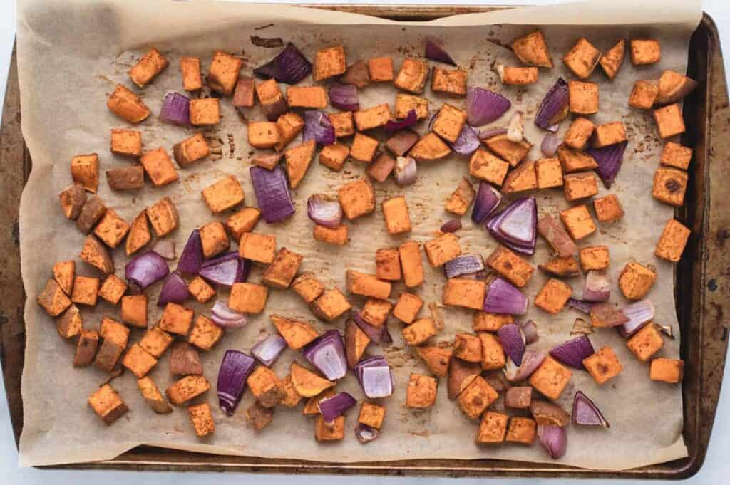 roasted sweet potatoes and red onions on a baking tray