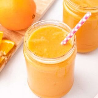 carrot orange smoothie in a glass jar with a straw