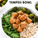 Spicy peanut tempeh with kale, broccoli, and rice in a bowl
