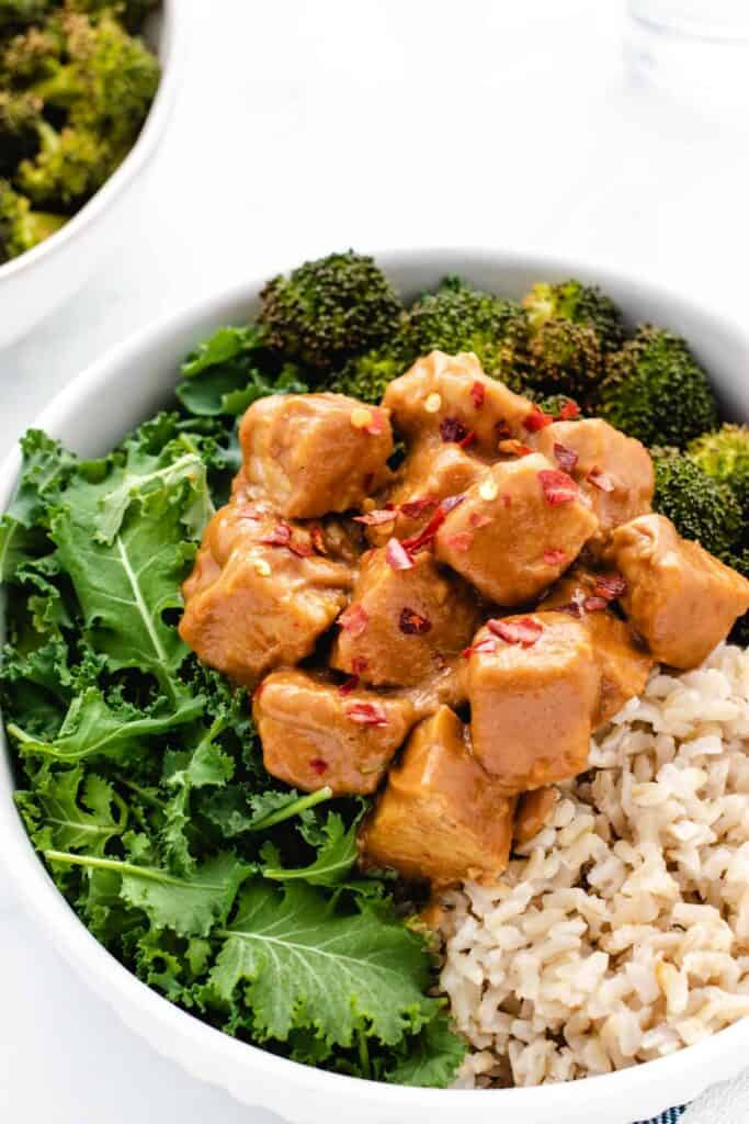 peanut tempeh bowl with kale, roasted broccoli, and rice in a bowl