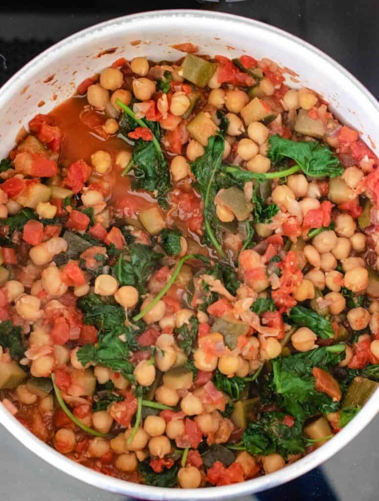 cooked chickpea stew with wilted kale
