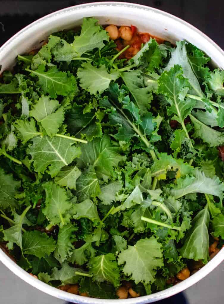 fresh kale in chickpea stew in a large pot