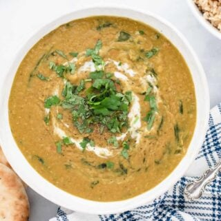 red lentil dal with cilantro and sour cream in a bowl