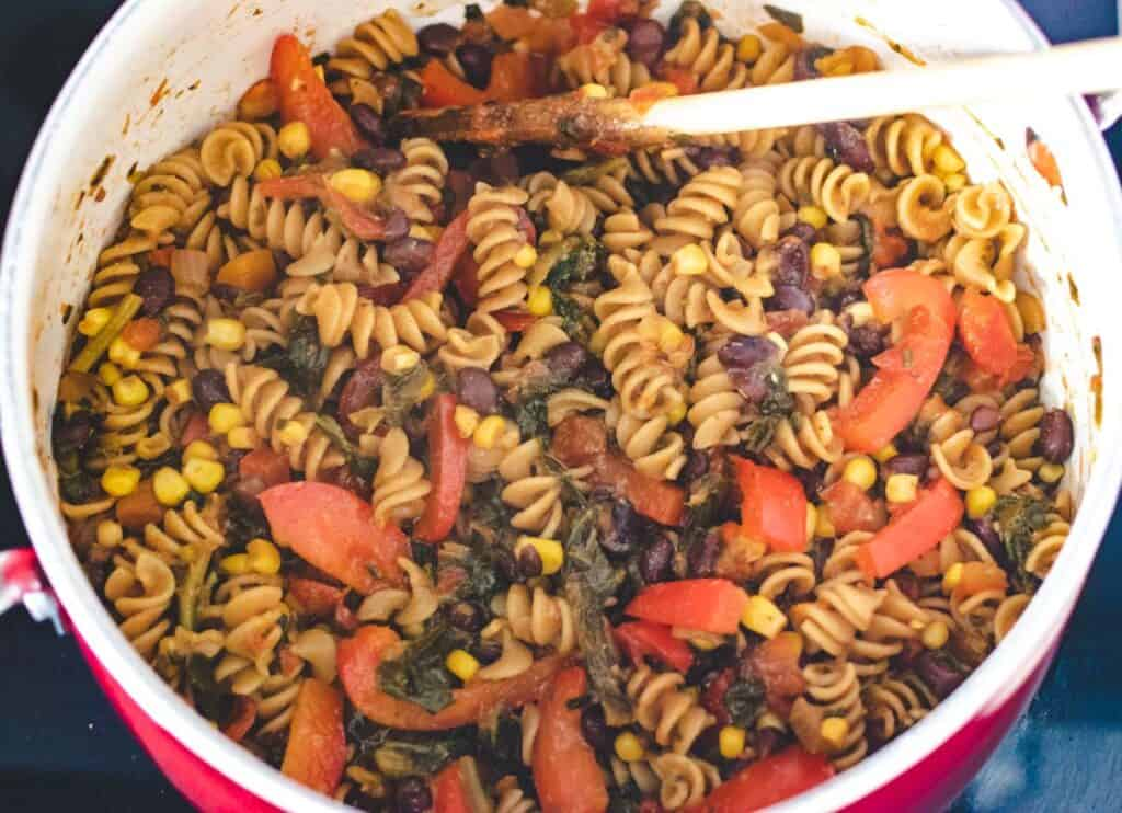one pot pasta with red bell peppers and black beans in a large pot.