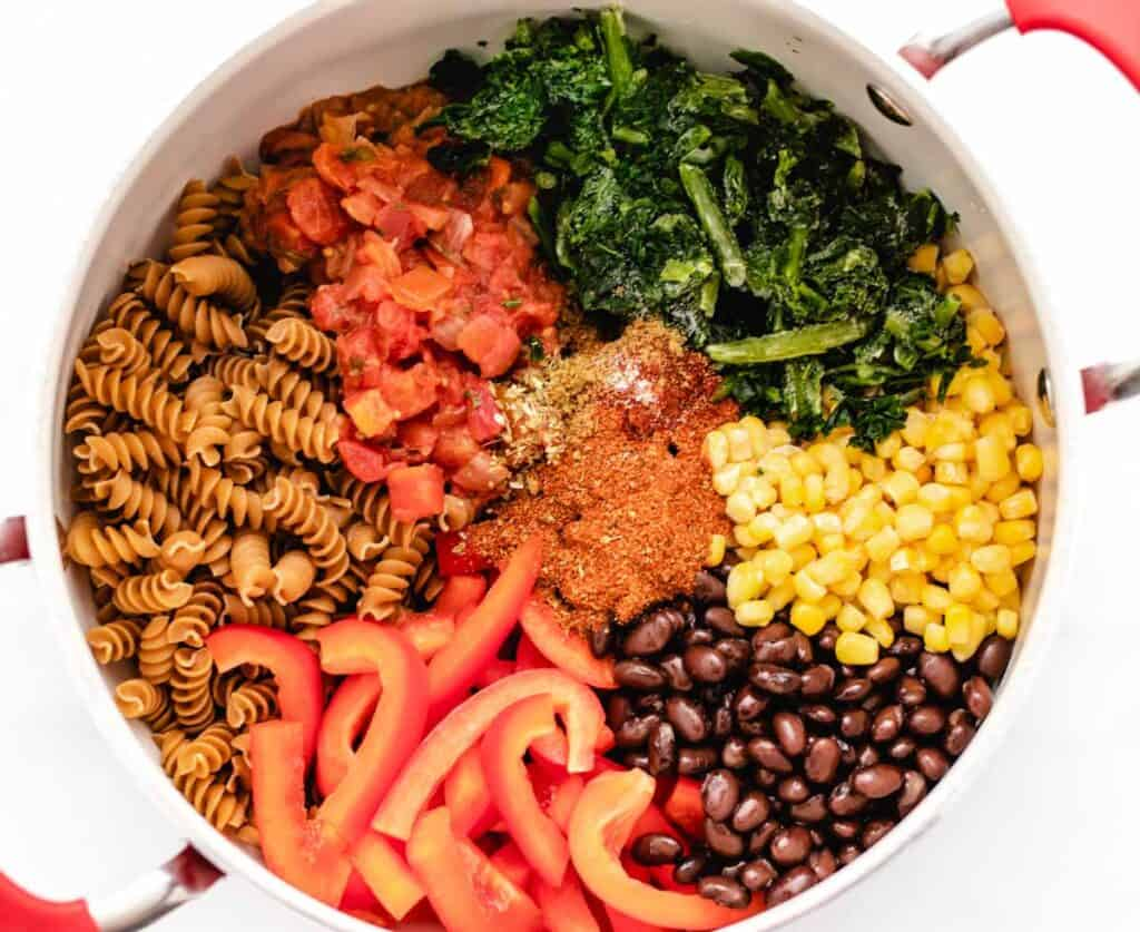 pasta, black beans, corn, red bell pepper, seasonings, salsa, and spinach in a large pot.