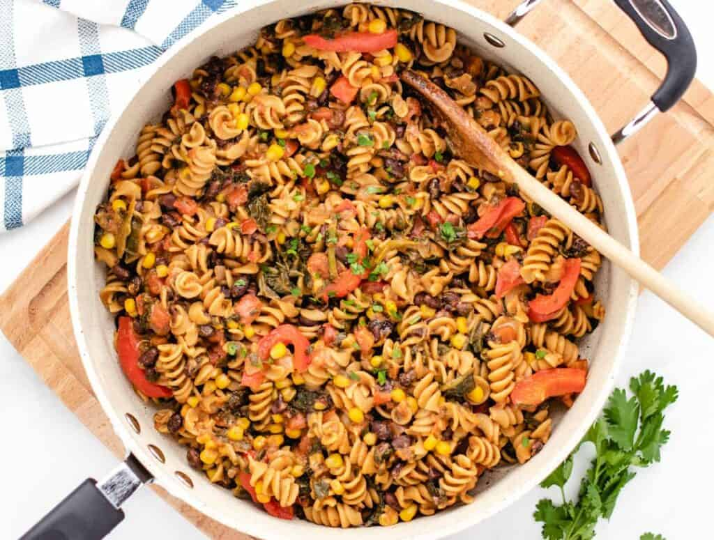 southwest pasta with black beans, corn, red bell pepper, in a pan with a spoon
