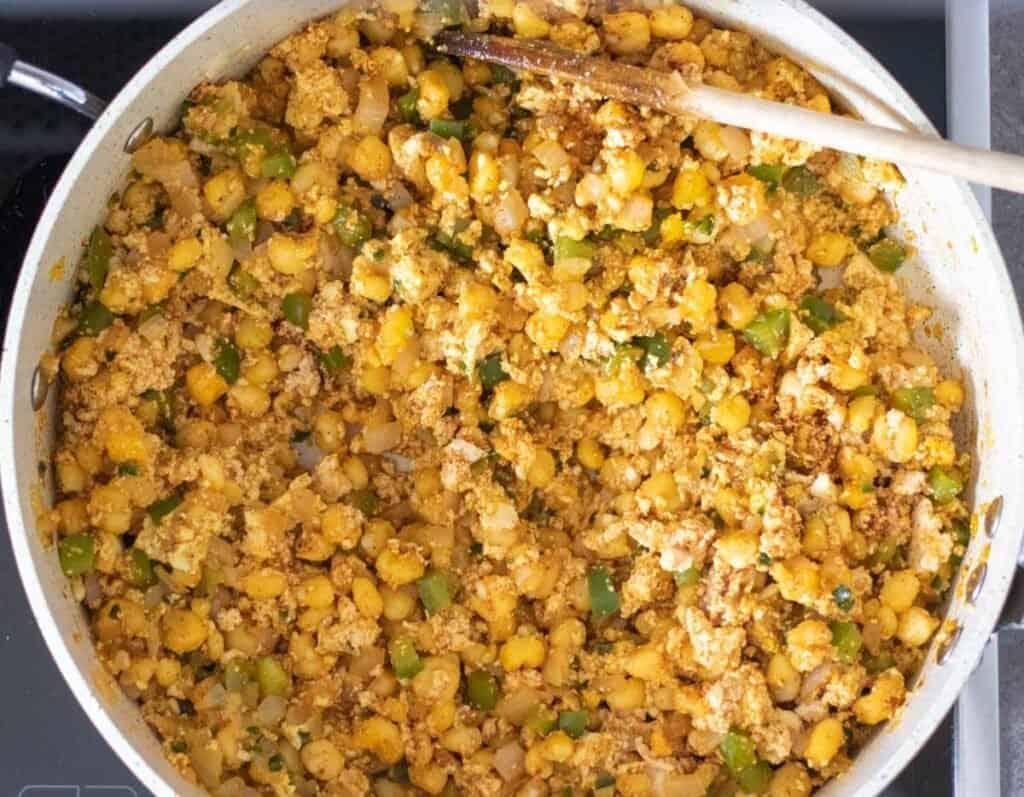 hominy, tofu, veggies, and seasonings cooking in a pan.