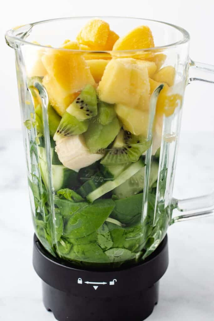 blender filled with spinach, banana, pineapple, cucumber and kiwi