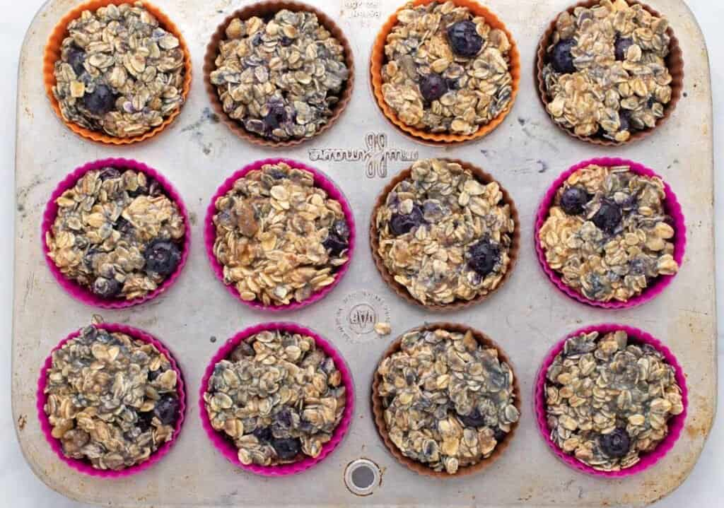 uncooked bluebery oatmeal cups in a muffin tray